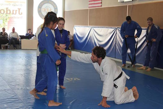 Canto helping Judo America girls